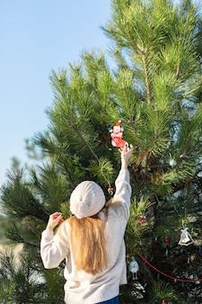 Mädchen verziert mit einem dekorativen spielzeug und girlanden einen grünen neujahrsbaum auf der straße im winter im wald. christbaumschmuck.