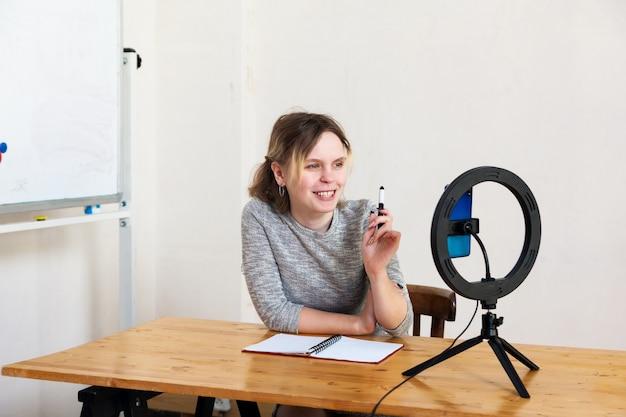 Mädchen von 16 jahren, das video auf smartphone aufzeichnet und sich mit ringlampe am tisch im hellen raum beleuchtet