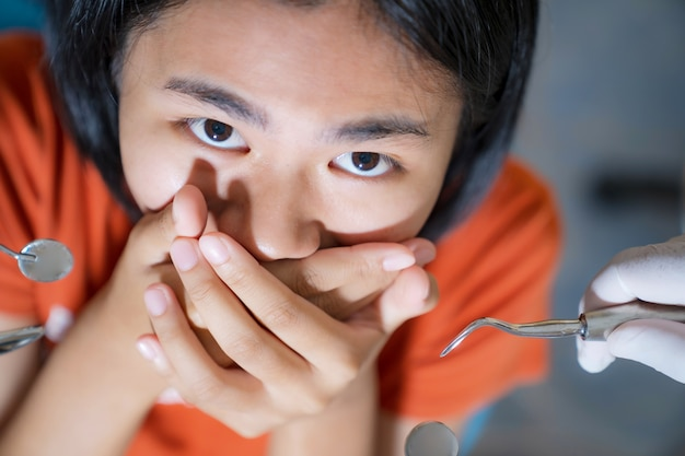 Mädchen von zahnärzten erschrocken bedeckt ihren mund in der zahnarztpraxis