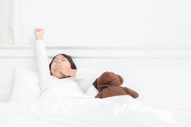 Mädchen wachen auf, gähnen und strecken auf bett