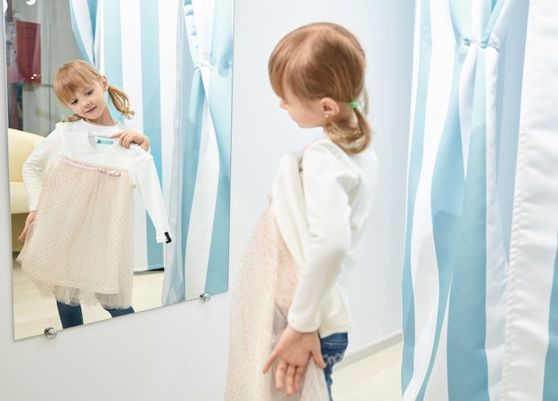 Mädchen wählen, versuchen, kleid in einkaufszentrum anzulegen, spiegel zu betrachten.