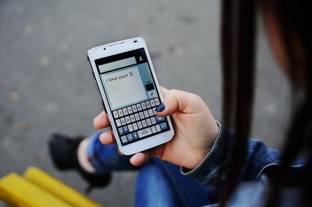 Mädchen wählt sms mitteilung am handy