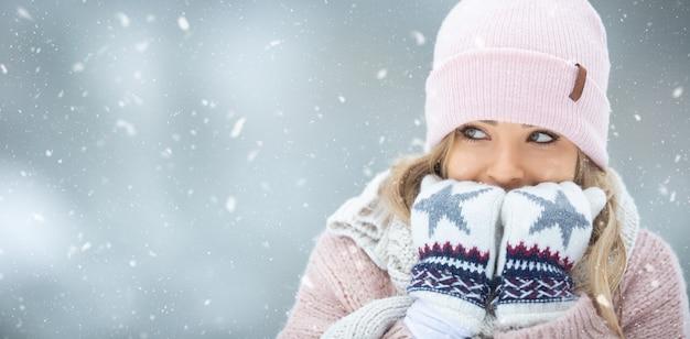 Mädchen wärmt ihre hände in handschuhen, indem sie ihnen warme luft einatmet.