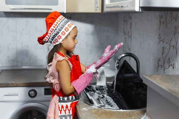 Mädchen waschen laptop im waschbecken auf küche