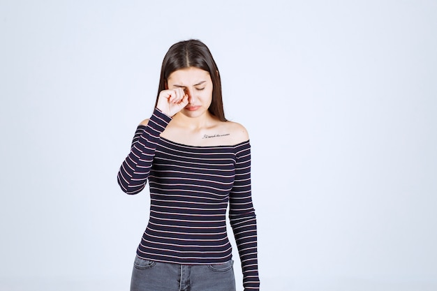 Mädchen weinen und ihre tränen mit der hand entfernen.
