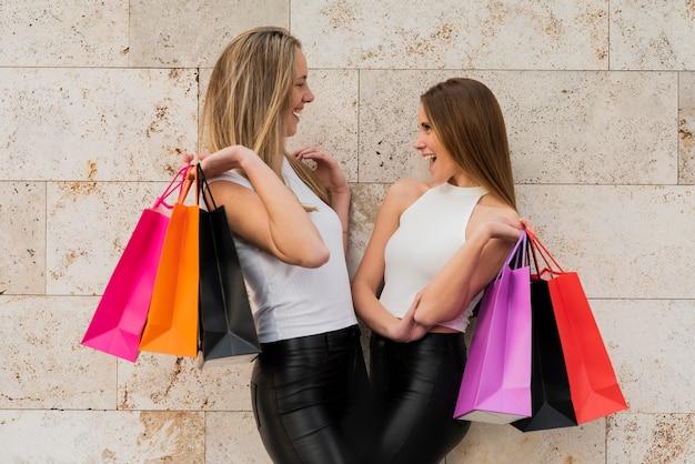 Mädchen, welche die einkaufstaschen betrachten einander halten