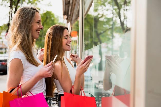 Mädchen, welche die einkaufstaschen betrachten schaufenster halten