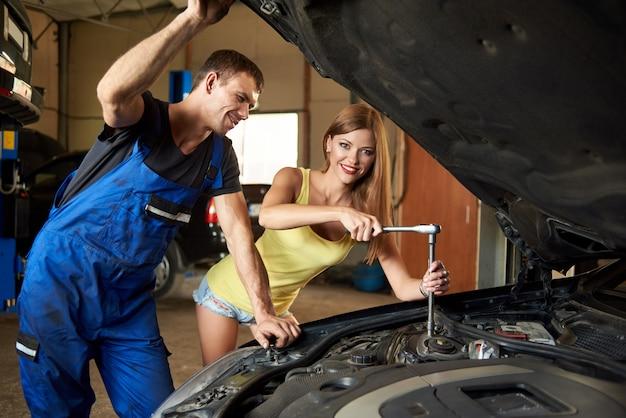 Mädchen, welches das auto mit einem schlüssel repariert