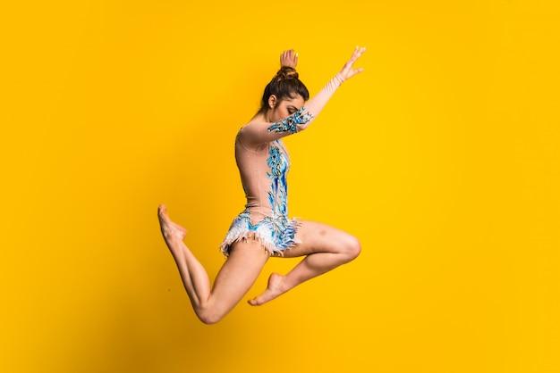 Mädchen, welches das springen der rhythmischen gymnastik tut