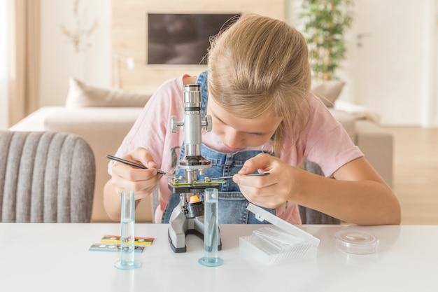 Mädchen, welches die chemie zu hause spielt mit dem mikroskop lernt
