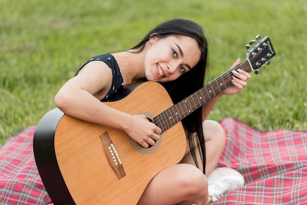 Mädchen, welches die gitarre auf einer picknickdecke spielt