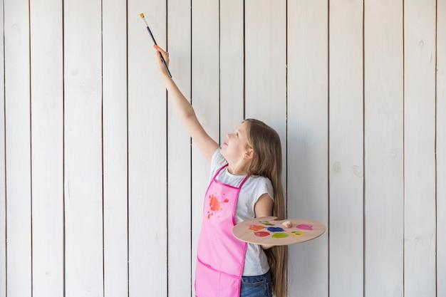 Mädchen, welches die hölzerne palette versucht zu malen auf hölzerner wand der weißen planke hält