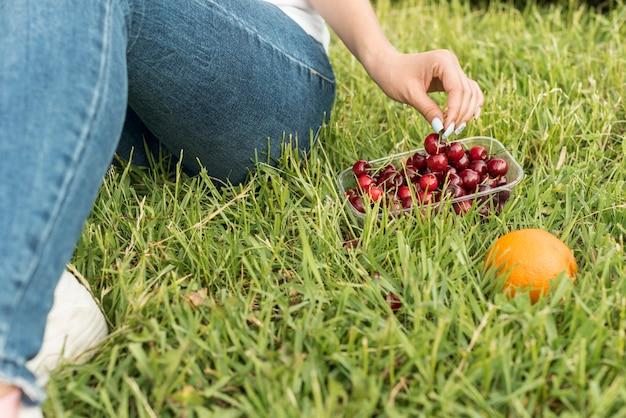 Mädchen, welches die kirschen sitzen auf dem gras nimmt