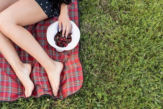 Mädchen, welches die kirschen sitzen auf picknickdecke nimmt