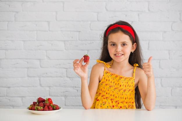 Mädchen, welches die rote erdbeere zeigt daumen herauf zeichen anhält