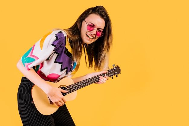 Mädchen, welches die ukulele spielt