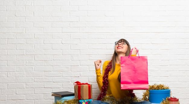 Mädchen, welches die weihnachtsfeiertage halten viele einkaufstaschen feiert