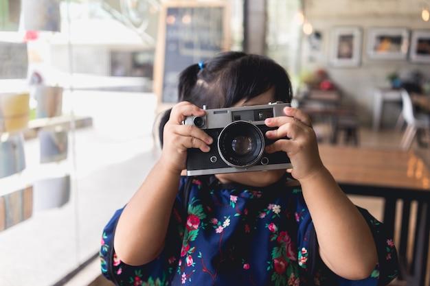 Mädchen, wenn sie eine weinlesefotokamera in den händen am kaffeecafé halten