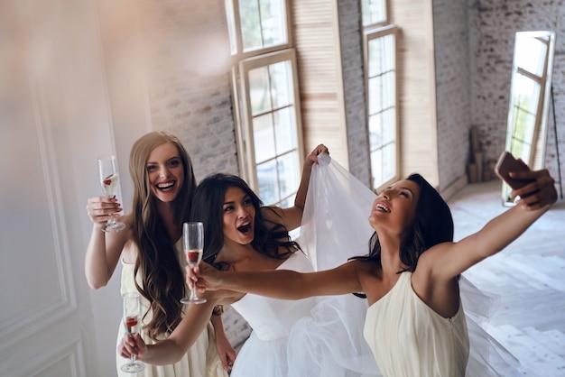 Mädchen werden verrückt. blick von oben auf die attraktive junge braut und zwei brautjungfern, die gesichter machen, während sie in der umkleidekabine selfies machen