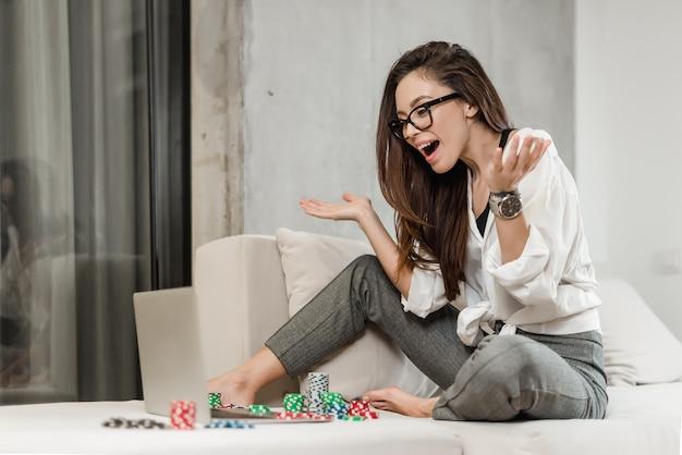 Mädchen wetten und online-poker spielen auf laptop, geld im internet-casino zu gewinnen
