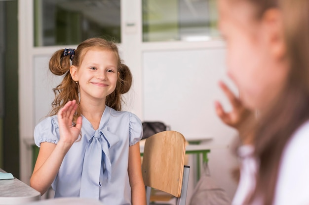 Mädchen winken einander zu und halten dabei soziale distanz