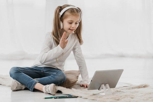 Mädchen winkt ihren virtuellen klassenkameraden zu