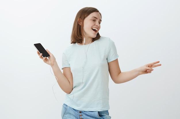 Mädchen wird echter star mit perfektem klang von kopfhörern. porträt der entzückten glücklichen und weggetragenen netten frau, die tanzend musik mitsingt, während lieder in den ohrhörern hören, die smartphone halten