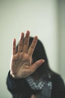 Mädchen wird geschlagen. junges mädchen mit prellungen auf ihrem gesicht, das stoppschild zeigt