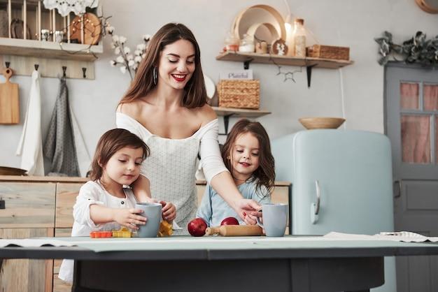 Mädchen wird nährsaft probieren. junge schöne frau gibt den kindern getränke, während sie mit spielzeug am tisch sitzen.