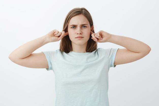 Mädchen wird nicht zuhören, die ohren zu schließen. intensive, ernsthaft aussehende, gestörte frau, die das hören mit zeigefingern bedeckt und gleichgültig und unbeteiligt steht und nicht bereit ist, das gespräch fortzusetzen