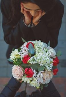 Mädchen wird vom mann überrascht, der einen blumenblumenstrauß anbietet