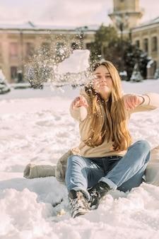 Mädchen wirft einen schneeball im sitzen