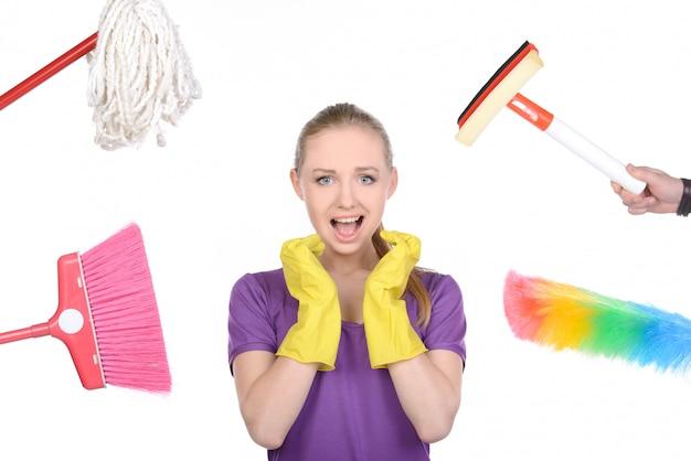 Mädchen wurde von geräten zur reinigung des hauses umgeben.