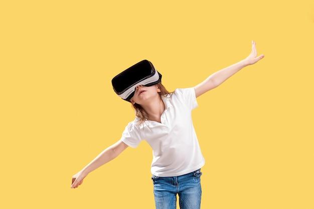 Mädchen yo in der formalen ausstattung, welche die vr-gläser setzen trägt, teilt in der aufregung aus, die auf gelb lokalisiert wird. kind, das ein spielgerät für virtuelle realität verwendet. virtuelle technologie