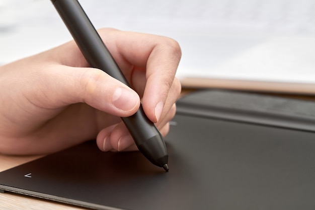 Mädchen zeichnet auf einem grafiktablett mit stift