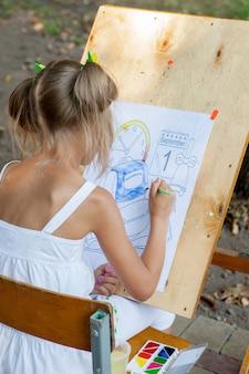 Mädchen zeichnet ein malbuch mit bis
