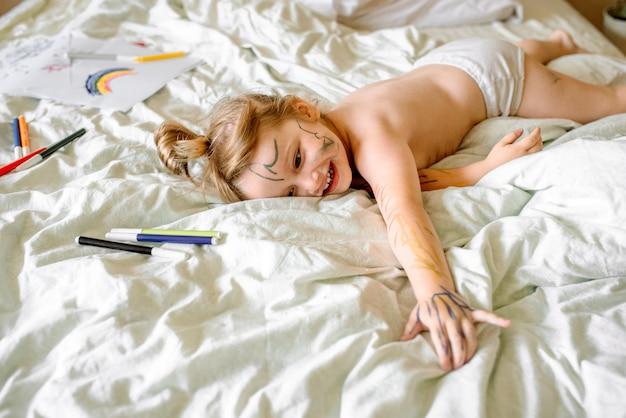 Mädchen zeichnet einen regenbogen auf weißem papier mit filzstiften auf dem bett. kinder spielen morgens zu hause. schelmisches ungezogenes baby, verschmierte hände, füße und gesicht in farben, schmutzig.