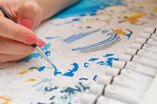Mädchen zeichnet mit einem pinsel malen nach zahlen auf einer leinwand aus nächster nähe