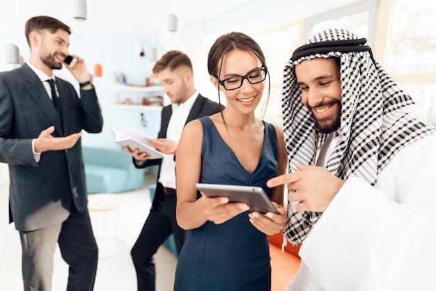 Mädchen zeigt einem mann in der arabischen kleidung auf einer tablette etwas.