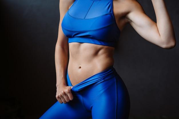 Mädchen zeigt ihre gepumpte bauchpresse. sportlicher körper nach diät und starker bewegung, schlanke taille
