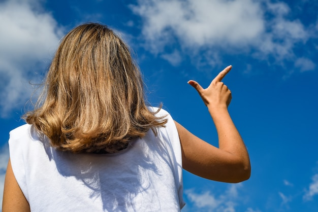 Mädchen zeigt mit dem finger gegen den himmel. rückansicht. warten sie lange silhouette richtung weg wählen sie landschafts resort ausflug konzept.