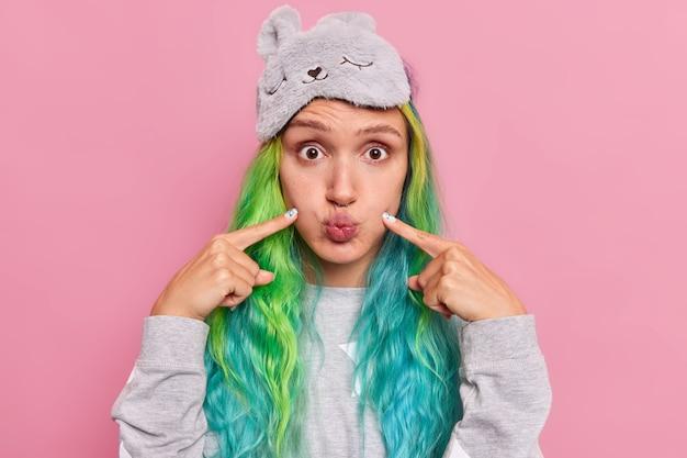 Mädchen zeigt mit dem zeigefinger auf blasende wangen macht lustige grimasse trägt schlafmaske und pyjama posiert auf pink