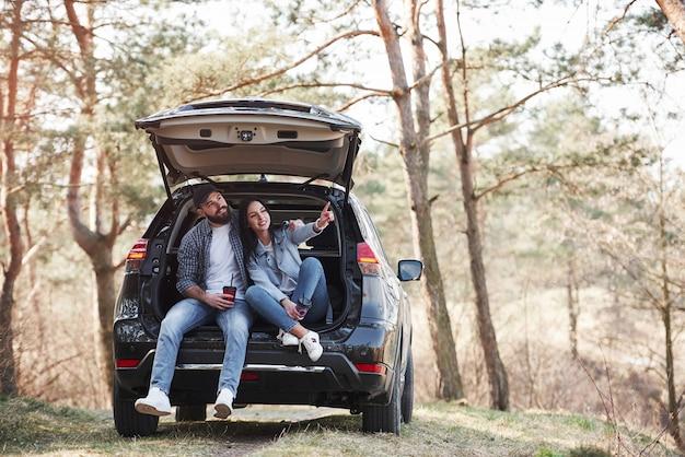 Mädchen zeigt nächstes ziel. sitzen auf dem hinteren teil des autos. die natur genießen. paare sind mit ihrem brandneuen schwarzen auto im wald angekommen
