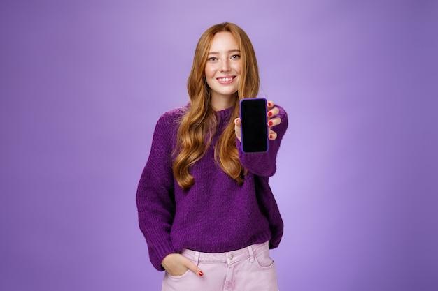 Mädchen zeigt smartphone-bildschirm an der kamera, um die meinung eines freundes zu fragen, der breit mit optimistischem und freudigem ausdruck lächelt und die hand in der tasche hält, um handy oder app auf violettem hintergrund zu fördern.
