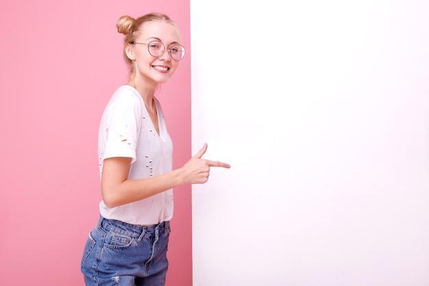 Mädchen zeigt weißes banner für text im studio