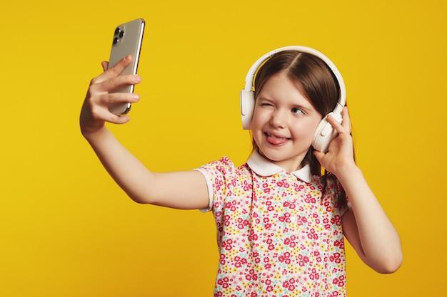 Mädchen zeigt zunge und macht selfie auf smartphone hört musik in