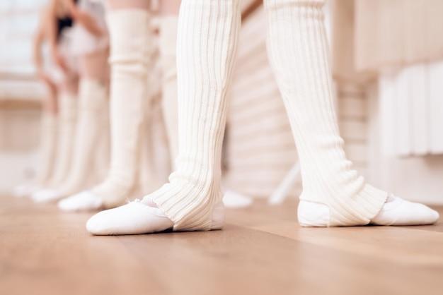 Mädchen ziehen weiße strumpfhosen und ballettschuhe an.