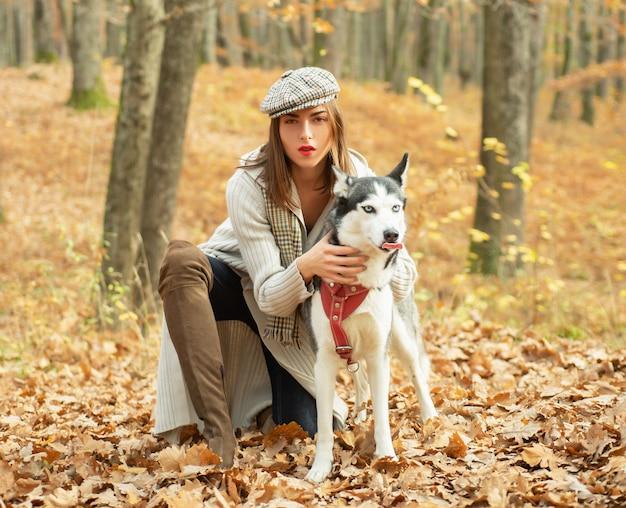 Mädchen ziemlich stilvolle frau, die mit husky hund herbstwald geht