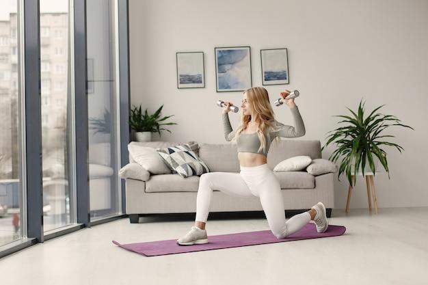 Mädchen zu hause. frau machen yoga. dame mit hanteln.