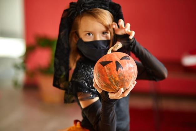 Mädchen zu hause im halloween-kostüm mit kürbis jack oder laurent in händen, kind trägt schwarze gesichtsmaske, die vor coronavirus schützt, halloween in quarantäne